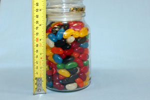 A tape measure next to a jar of jellybeans.