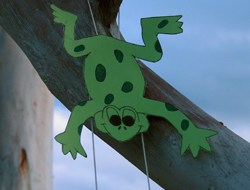 A paper frog attached to two strings in a tree.