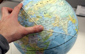Someone is holding a string on the surface of a globe of the world.