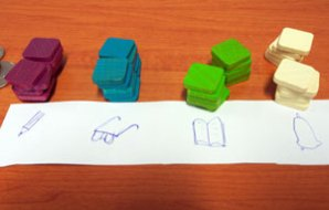 Purple counters near a pencil, blue near glasses, green near a book and white near a bell.