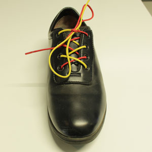 A shoe with red and yellow laces and a wonky bow.