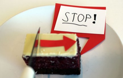 A knife is movine along a rectangular cake. There is a speech bubble saying 'stop'