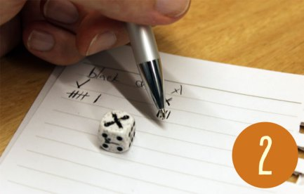 A dice with a cross on top. Someone is recording the result with pen and paper.