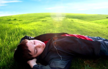 A bouy sleeping in the sunshine, on a green hill.