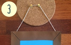 A cork board with two pins in it. a string goes around them.