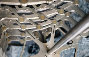 Close up image of the stainless steel gears of a clock.