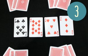 Four face-up playing cards on a table, and four piles of three face-down cards arranged around the outside.