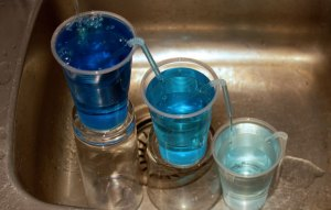 Three cups of blue liquid, sitting on upturned glasses connected by straws. The cups are cascading from highest on the left to lowest on the right and the liquid is darkest in the left cup and palest in the right cup.