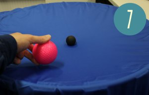Placing the larger pink ball onto the blue fabric with the small black ball.
