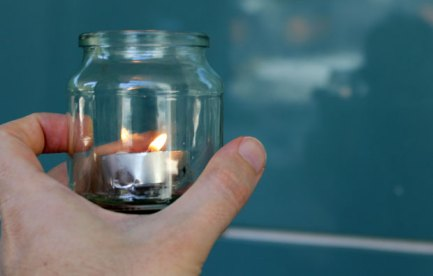 Image of a tealight in a small glass jar.