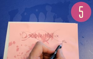 somoenoe drawing a logo on a pink sheet of paper