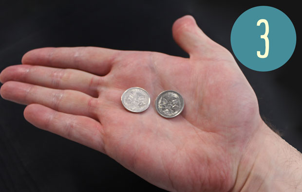 Two five cent coins in the palm of a hand.