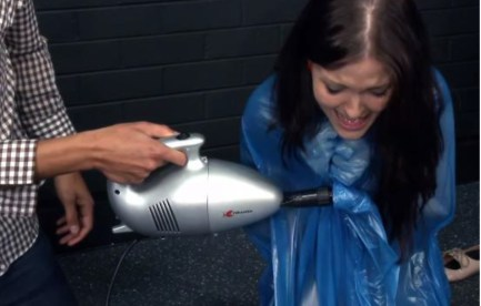 Woman in blue bag with head peeking out. Vacuum cleaner sucking air from bag.