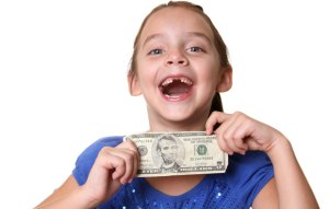 Girl with a missing tooth, holding some money