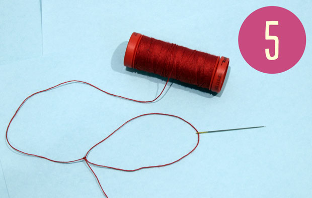Needle on a loop of red cotton thread.