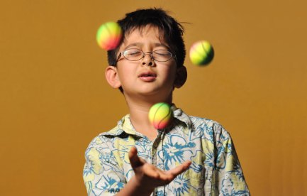Photo of a young boy with his eyes shut, juggling three balls.