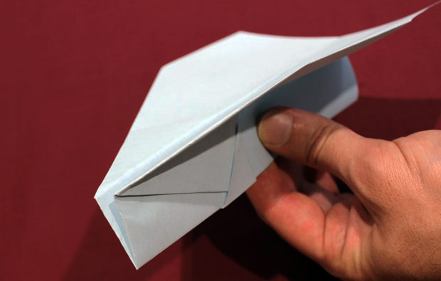 A white paper plane held in one hand.