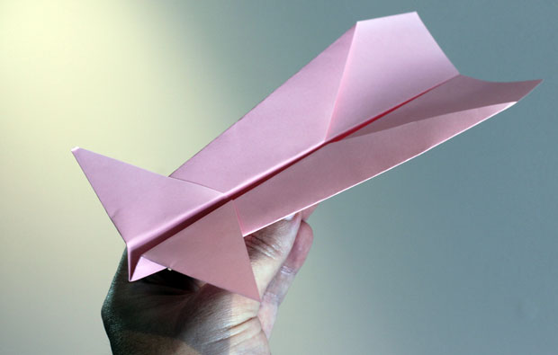 A pink paper plane with two sets of wings