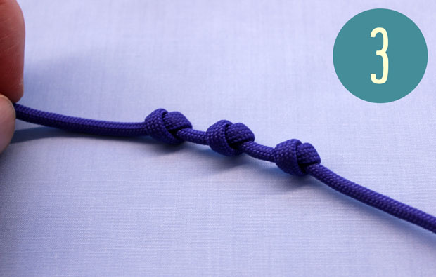 Purple string with 3 evenly spaced knots.
