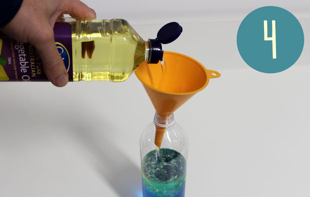 Pouring cooking oil into a bottle half filled with blue liquid.