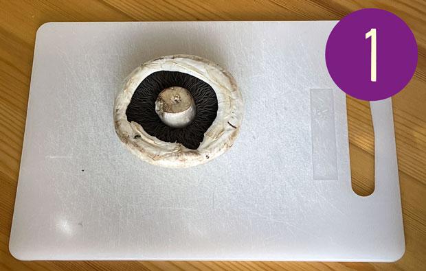 Mushroom on a chopping board, gill side up.