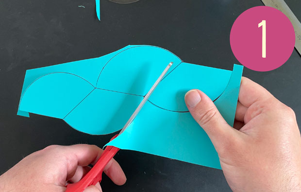Cutting out the curves with scissors.
