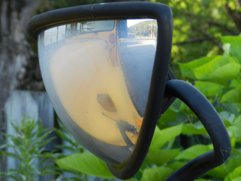 photograph of school bus seen through a convex mirror