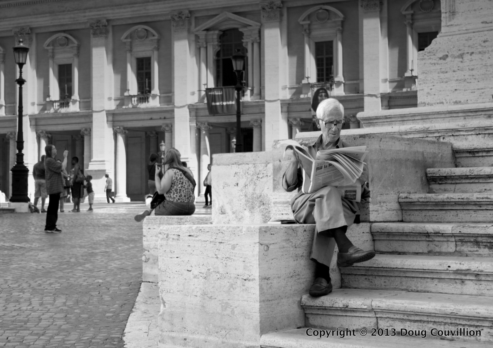 black and white photograph of a man reading the newspaper in Rome, Italy
