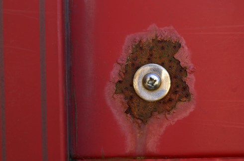 photograph of a bolt surrounded by rust