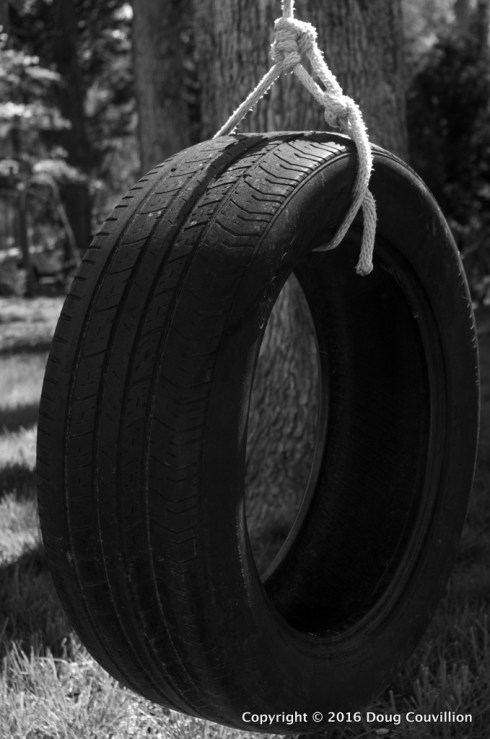black and white photograph of a tire swing
