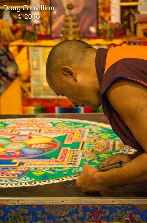 photograph of a Tibetan monk concentrating on adding sand to a mandala
