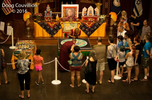 photograph of a crowd watching Tibetan monks make a mandala