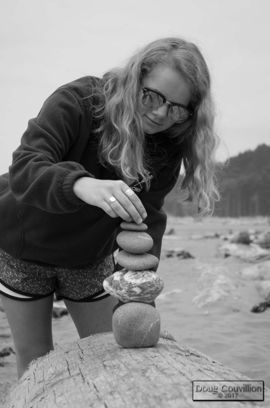 black and white photograph of a girl stacking stones on a beach in Washington by Doug Couvillion