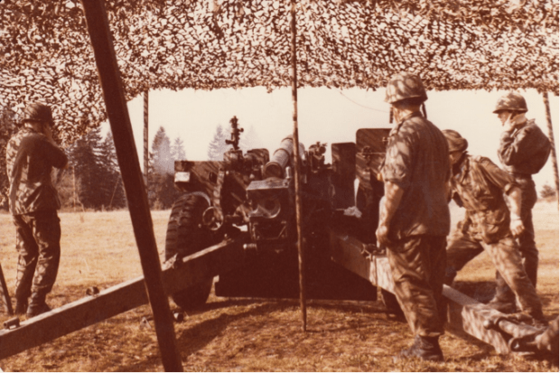 sepia photo of armed forces gathered behind a mortar