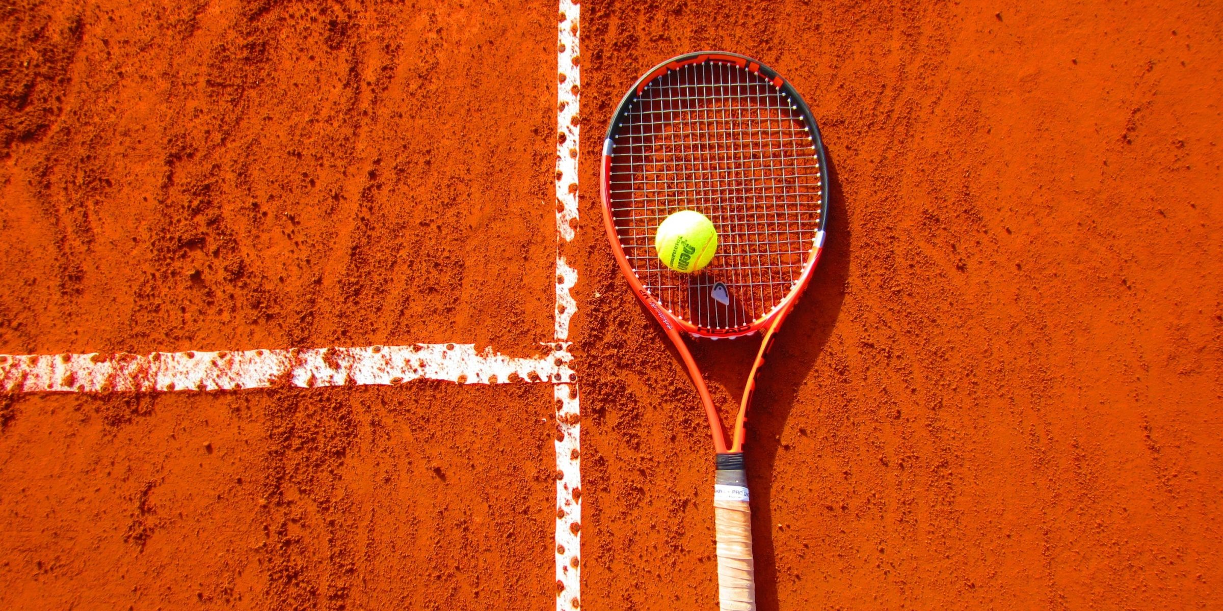 Photo of a red, black and white tennis racket with a yellow tennis ball on top. Set on an orange background.