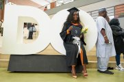 "A colour coordinated grad poses with the iconic ""DO"" in the New Westminster Campus concourse, Feb. 22."