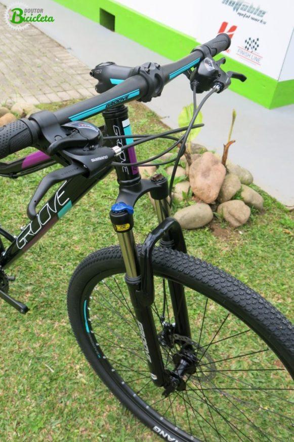 """Detalhes no avanço e guidão deixam a bike harmonizada com as cores do quadro. Destaque para os pneus Chaoyang, aros de 29"""" e suspensão com trava."""