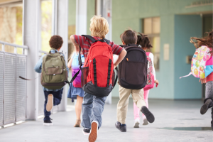 Elementary school kids running with backpacks