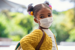 Little girl with a mask on ready for school