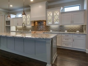 White kitchen cabinets with gray island