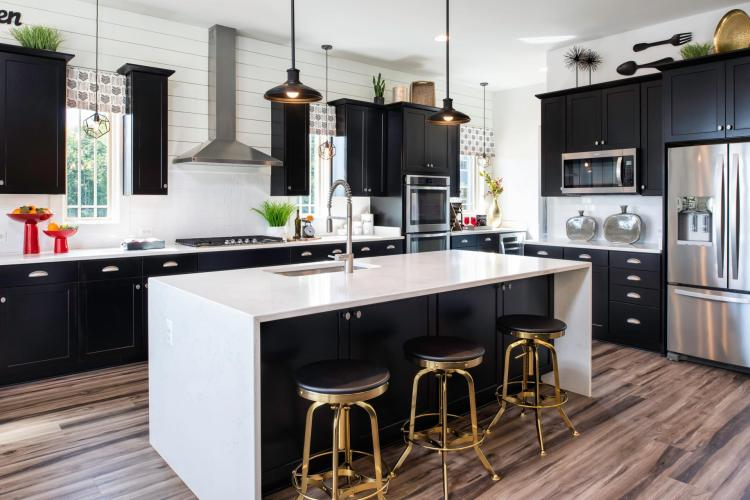 The Rowan kitchen featuring black cabinets and a waterfall island by Drees Homes in Washington D.C.