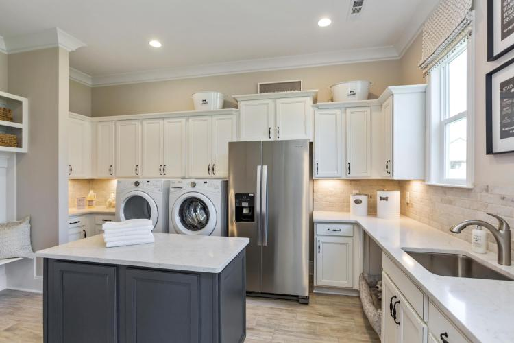A family ready room featuring a washer and dryer, refrigerator, cabinetry and an island | By Drees Homes