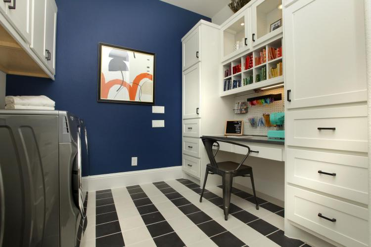 A family ready room featuring a washer and dryer, cabinetry and a pocket office | By Drees Custom Homes