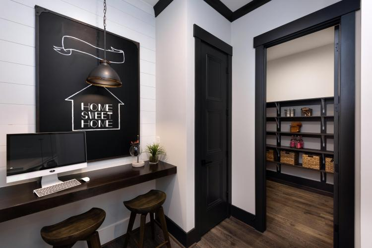 A pocket office featuring a slim desk and stools, located off the kitchen, near the walk-in pantry | By Drees Homes