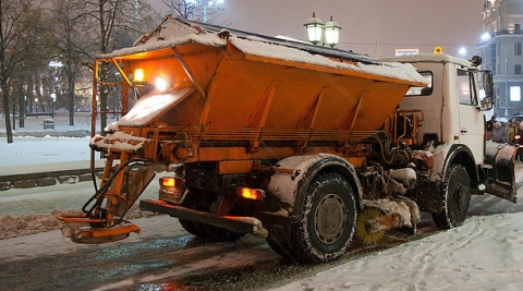 A snow plow spreads salt to melt ice on the road. (click for credit)