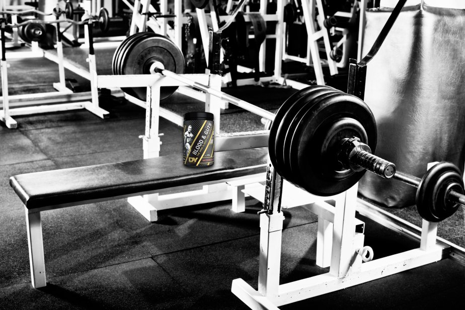 In this picture you can see a Blood and Guts Pre-workout on a gym bench.