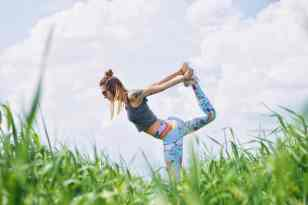 girl in the grass doing yoga wearing printed pants and a crop shirt