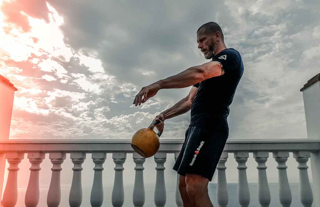 man outside working out with kettle bell