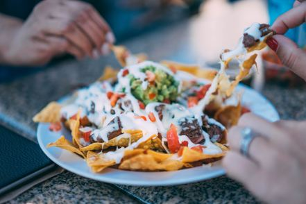 hands grabbing for nachos
