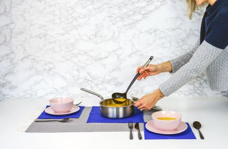 female arms serving soup from pot with ladle
